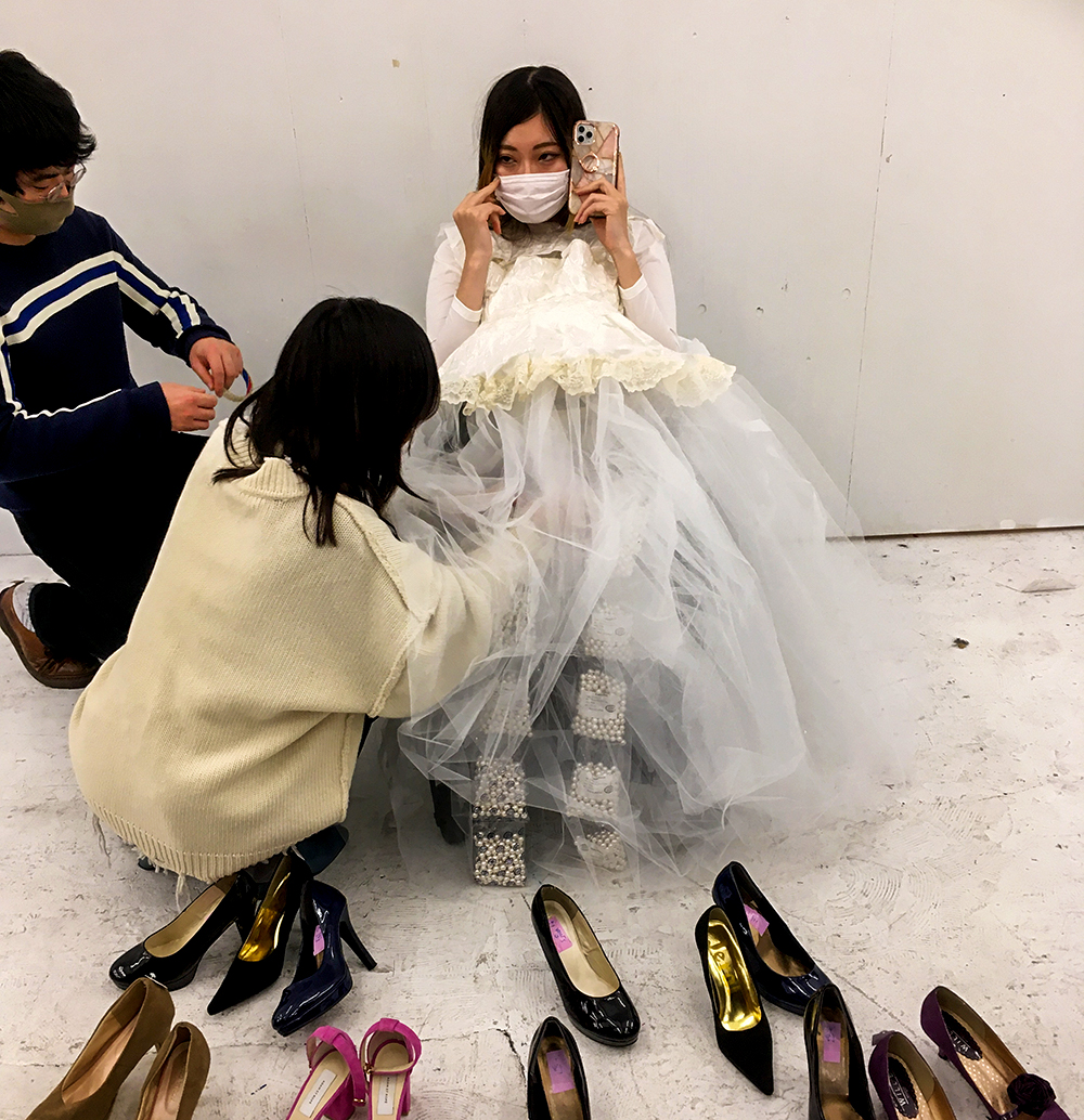 白いドレスをフィッティングするモデルの葦原海さんと、葦原さんの横についてドレスの調整をする田畑さん