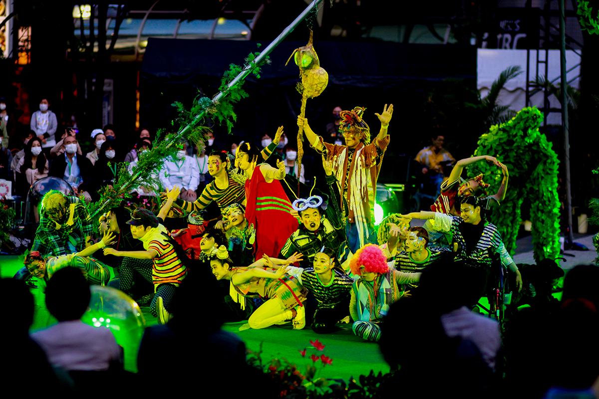 True Colors CIRCUSのリハーサルの様子。虫の衣装を纏った出演者たちがステージ中央に集まり緑のライトで照らされている