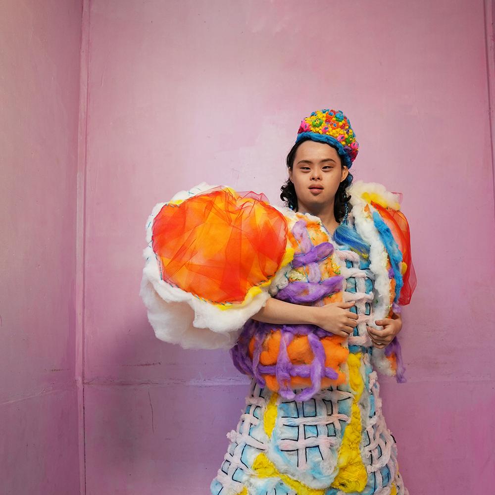 完成した衣装を身につけてポーズをとるカイト君。衣装はオレンジや水色やピンクなどポップな色使いとふわふわした素材感が特徴。