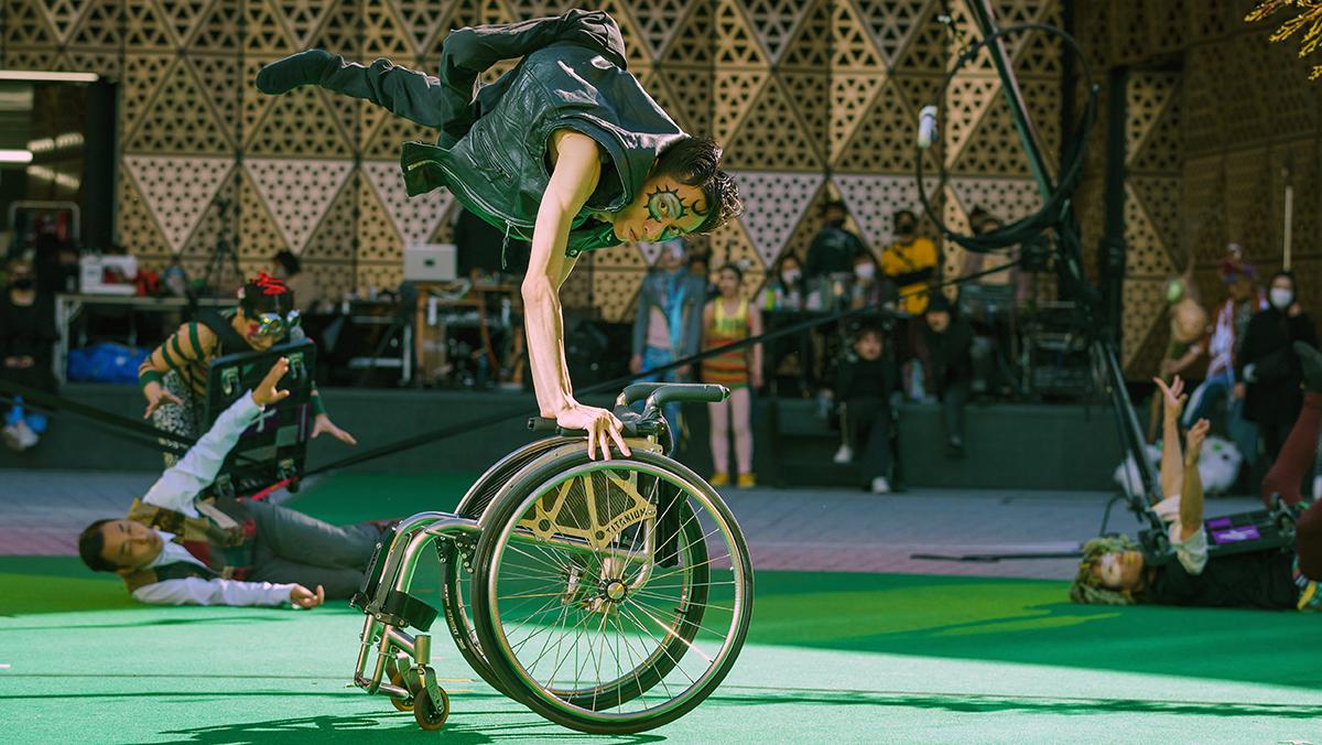 「True Colors CIRCUS」リハーサル風景。かんばらさんが車椅子の手すりに掴まって足をあげ、体全体を空中に持ち上げている。撮影:冨田了平