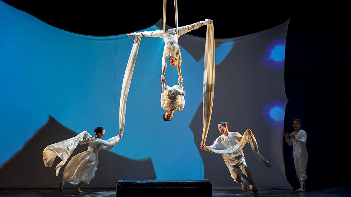 「SLOW MOVEMENT -Next Stage Showcase-」(主催:スロームーブメント実行委員会)の様子。舞台上でパフォーマーと両手をつなぎ、逆さまで宙吊りになるかんばらさん 撮影:Kazue Kawase