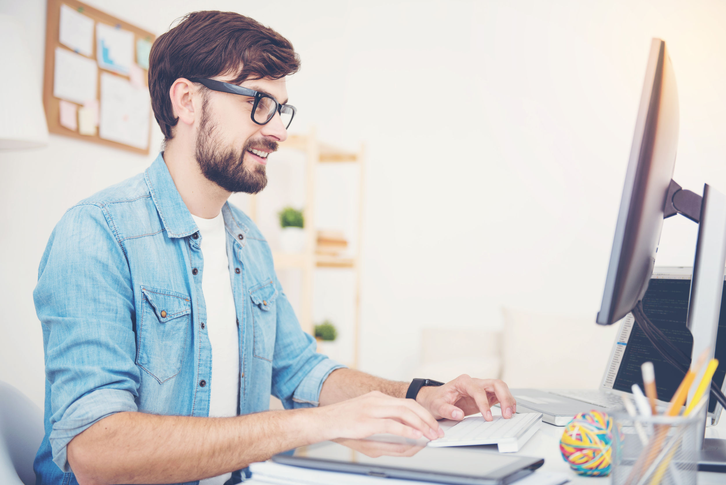 64095839 - it goes good. smiling young successful man wearing glasses programming in an office while using computer and laptop.