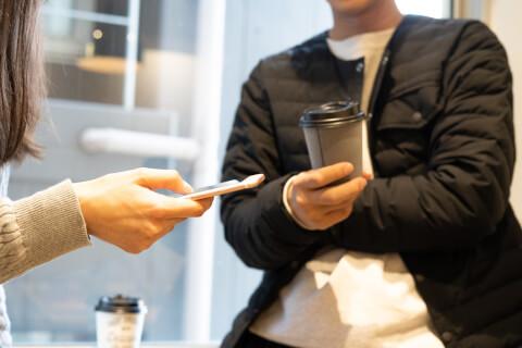スマホを持つ女性と紙コップを持つ男性