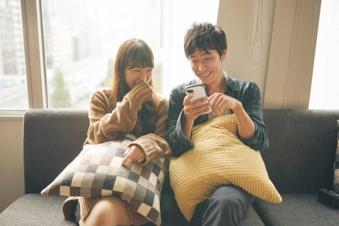 ソファに座ってスマホを見るカップル