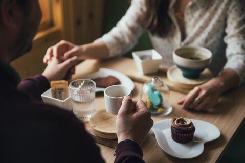 テーブルの上で手を握り合うカップル