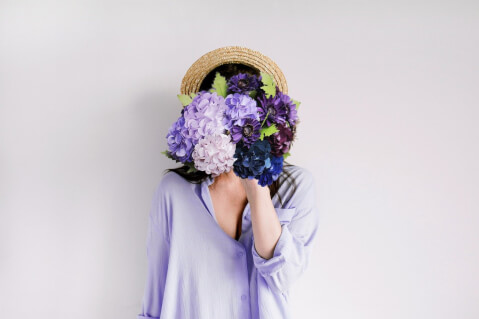 花束で顔を隠す女性