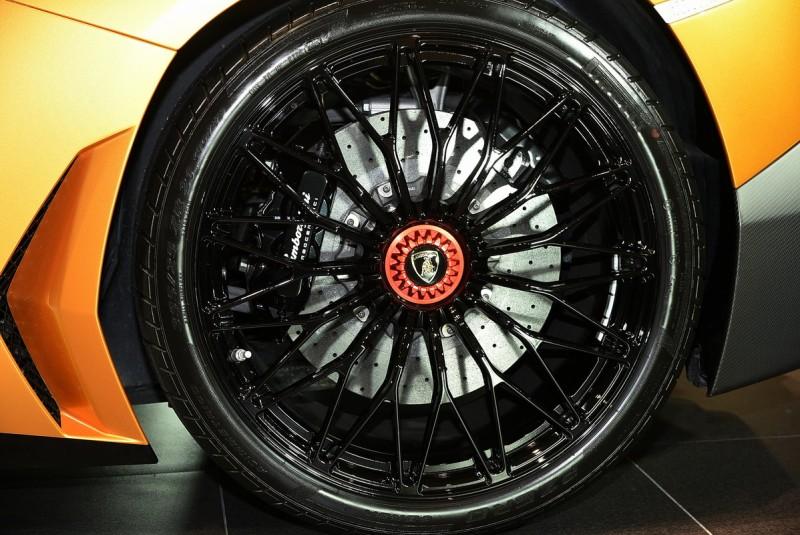 車尾45度相機放低拍果然霸氣十足,SV車型特殊標配的Dione鍛造消光鋁圈用點狀光源基本上很難打亮,但是補燈後輪圈中央的紅色競技化快拆單螺絲與裡頭的陶瓷碳纖碟盤卻是更清楚,而前255/30 ZR20與後355/25 ZR21的配胎組合直接點明了四驅底盤的Aventador SV LP 750-4應該具備偏向後軸或可以100%後驅的輸出個性,扁平比25的胎圈真的很少見阿