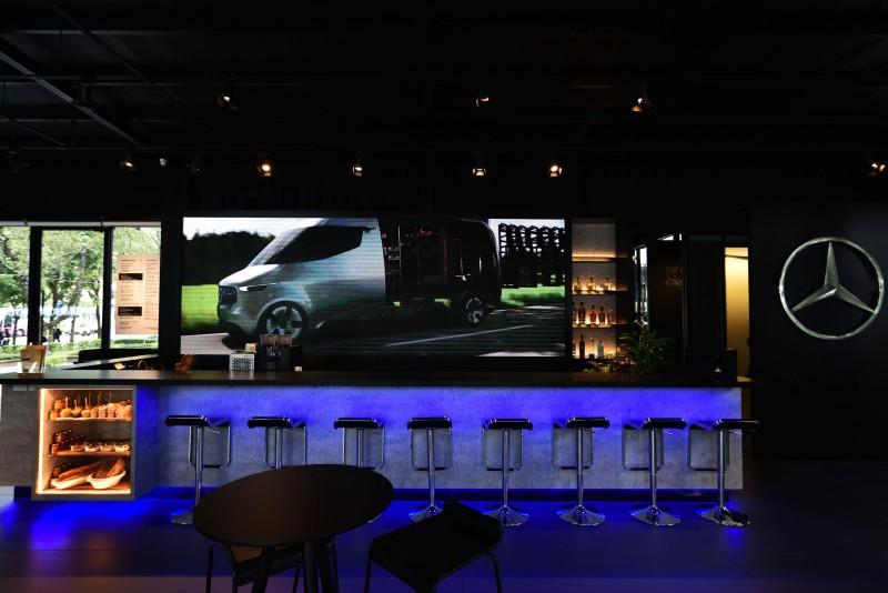 藍冷光色調的吧檯區搭配後方巨大的LED螢幕塑造未來科技感。