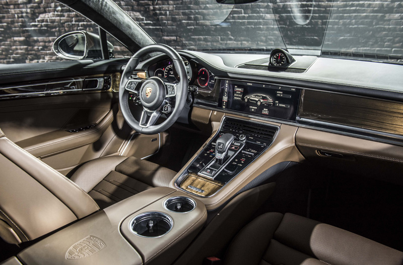 展示之Panamera Turbo Sport Turismo配置的新幾內亞胡桃木內飾板與黑/棕雙色內裝、前中央扶手盾形徽飾印記,以及跑車計時套件皆為選配件。