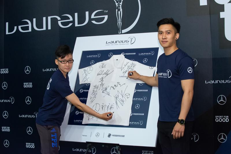 運動好手陳映竹(左)、連德安在勞倫斯紀念衣上簽名,邀請更多台灣運動員一同用運動改變世界。