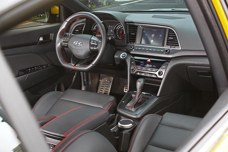 跑車式平底方向盤搭配運動化座椅與多處紅色縫線妝點,兼顧熱血與舒適雙重氛圍。