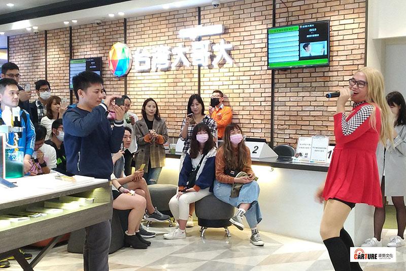 那那大師(右)在「台灣大哥大門市」扮賽車女郎快閃演唱,粉絲們也玩得很盡興。