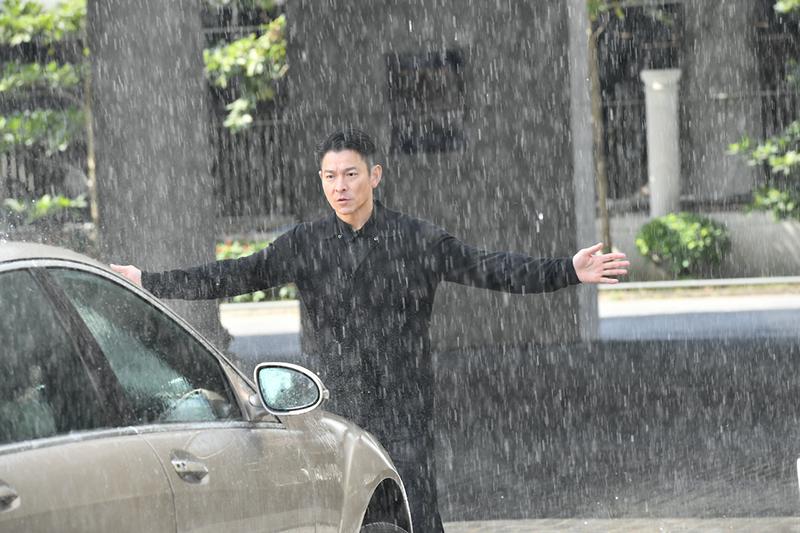 【車勢星聞】電影《熱血合唱團》中劉德華拼命大雨中攔車。(圖:双喜電影提供)