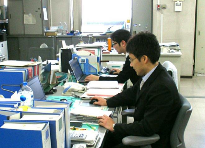 役所内で仕事をする男性2名