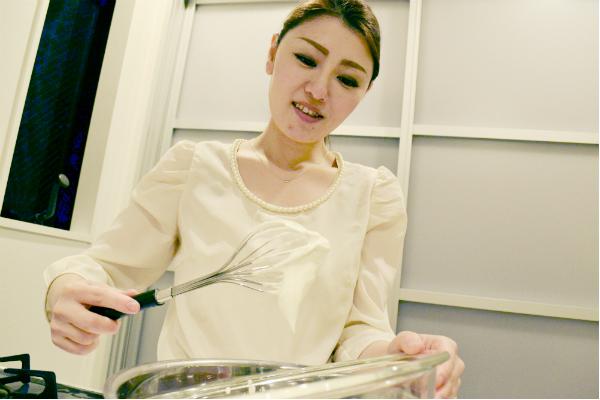 ホイップクリームの泡立ちを確認する女性