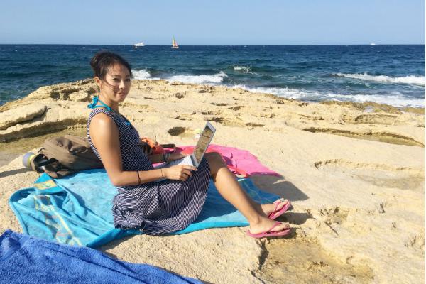 海岸でパソコンを開く女性