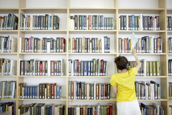 本棚で本を探す女性