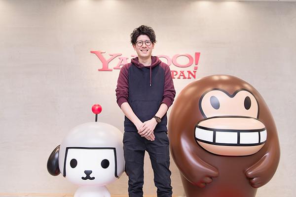 Yahoo!ロゴの前の岡さん
