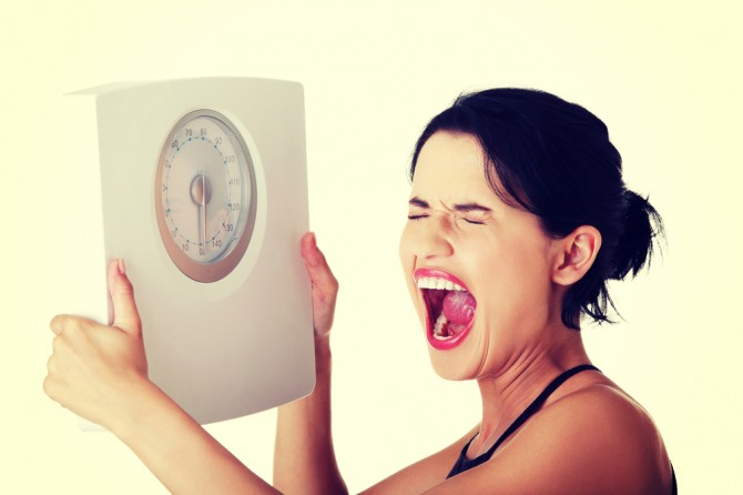 体重計をもって叫ぶ女性