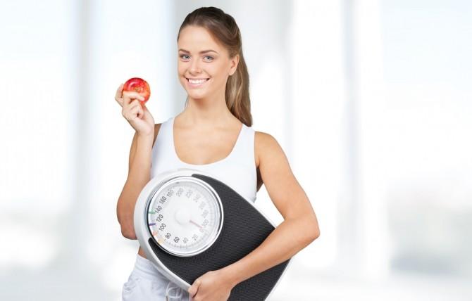 体重計とリンゴを持つ女性