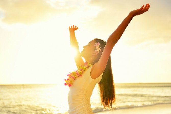 海の前で健康的な伸びをする女性