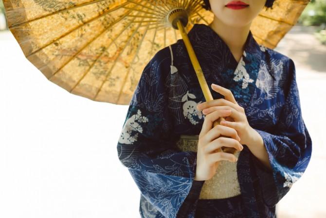 紺の浴衣を着て和傘を持つ女性