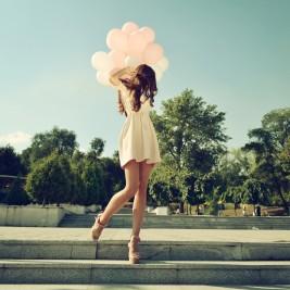 風船を持つ脚が綺麗な女性