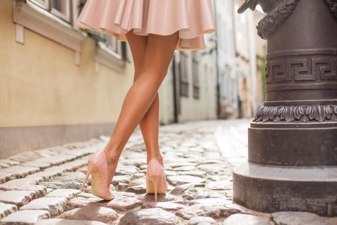 ヌーディーカラーのスカートとヒールを履いた女性