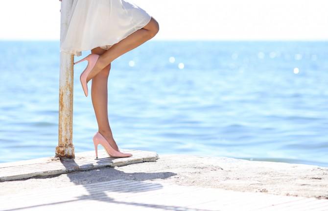 海辺でヒールを履いている女性