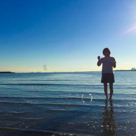 浅瀬の海でシャボン玉を楽しむ女性