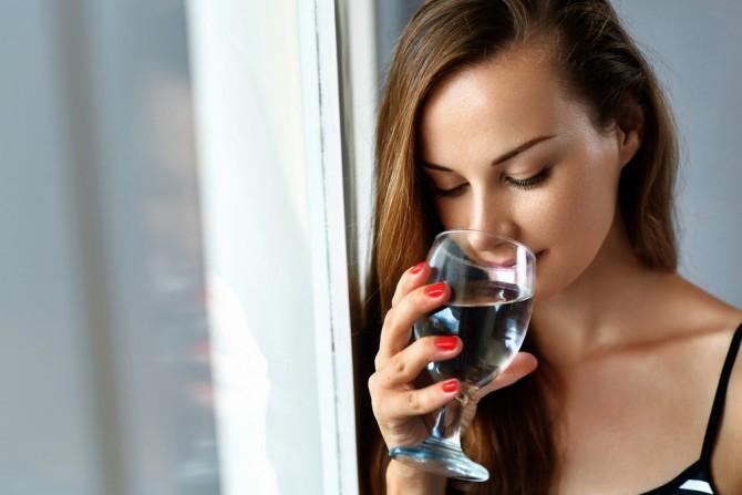 ワイングラスで水を飲む女性