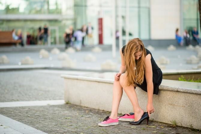 スニーカーから黒いヒールに履き替える女性