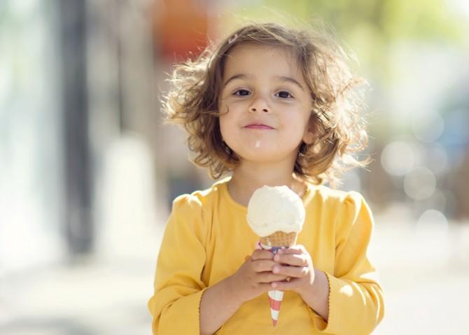 アイスクリームを持つ満足気の少女