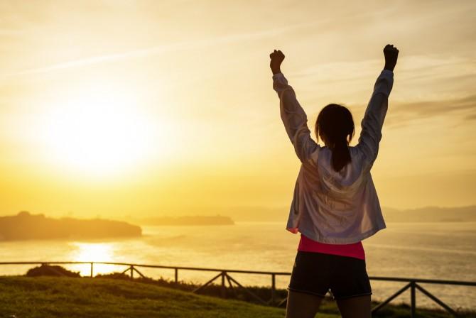 山頂で達成感による両手を挙げる女性