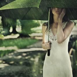 雨の中、白いワンピースを着て傘をさす女性