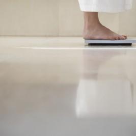 遠くの方で体重計にのる女性の脚