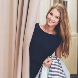 若い金髪の女性が試着室前でほほえむ