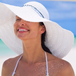海辺で日差しを浴びる白いハットをかぶる女性