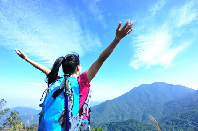 山の上で両手を広げる女性