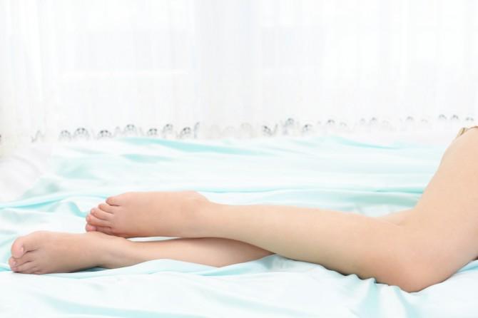 水色のシーツの上にある足