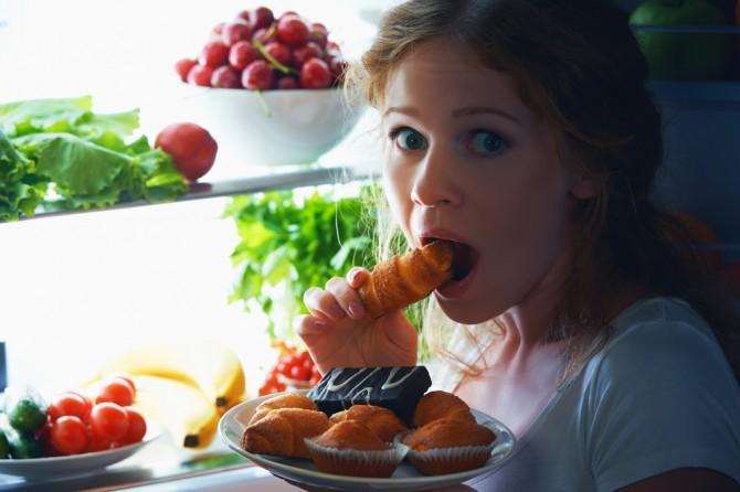 冷蔵庫の食材を食べる女性
