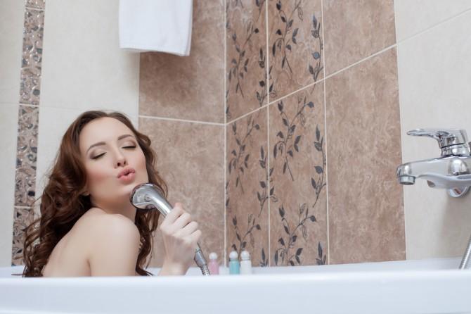 バスタブの中でシャワーを浴びる女性