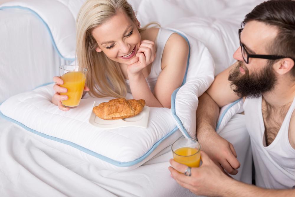 ベッドでほほえましく朝食をとる男女