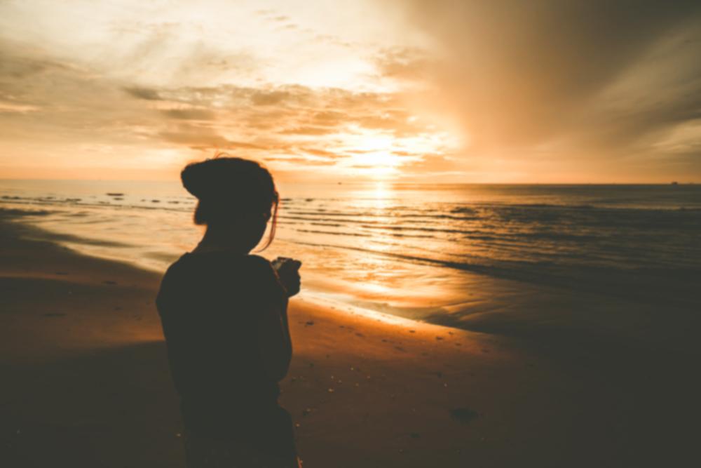 海辺の夕焼けとシルエットの女性