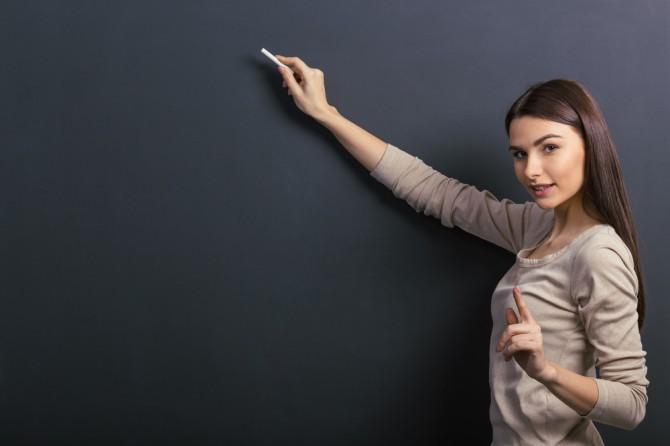 黒板に注意を書く女性