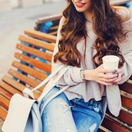 ベンチに腰掛けるニット服の女性