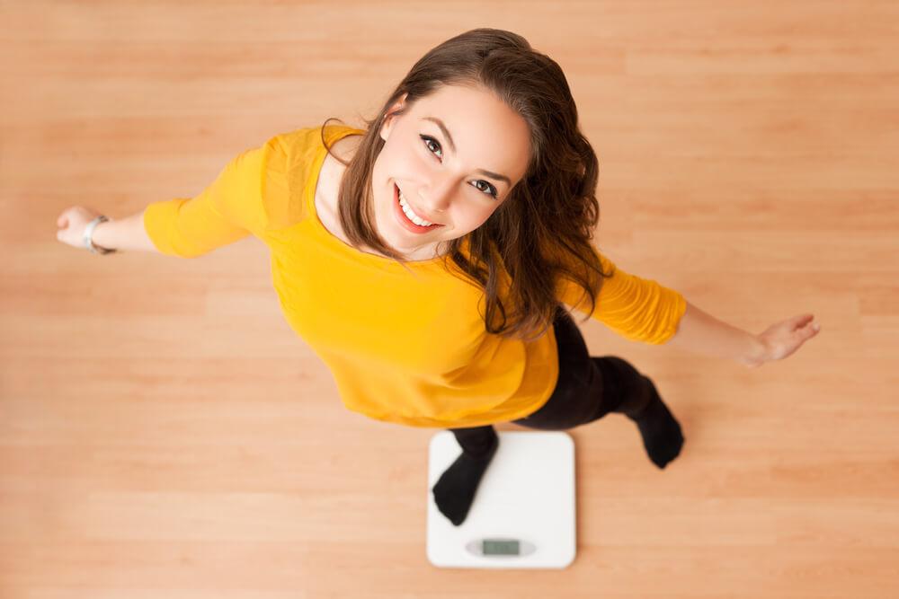 笑顔で体重計に乗る女性