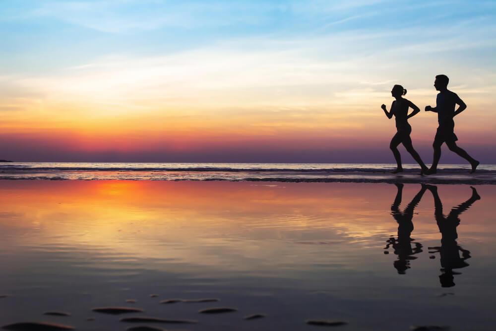 夕暮れの海辺を走る男女