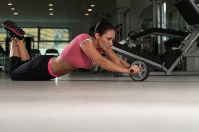 腹筋ローラーで伸びる女性