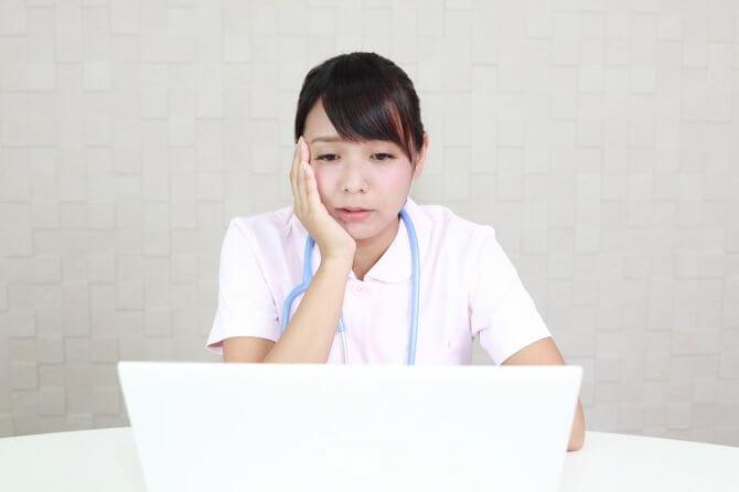 PCを見て落ち込む女性